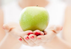 Female hands with green apple Royalty Free Stock Image