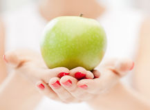 Female hands with green apple Royalty Free Stock Photos