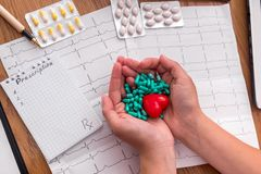 Female hands with green capsules and red heart.  royalty free stock photography