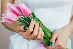Female hands with green manicure holding pink tulips, close-up Royalty Free Stock Photo