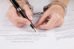 Female hands in handcuffs fill the contract Royalty Free Stock Photography