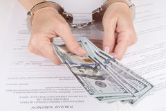 Female hands in handcuffs hold dollars Stock Photo