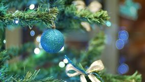 Female hands hanging balls on the Christmas tree. Winter holidays Christmas and New Year Decoration. Blinking Garland. Female hands hanging balls on the stock footage