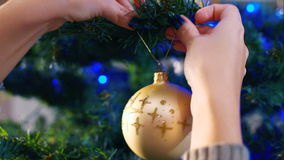 Female hands hanging balls on the Christmas tree stock video