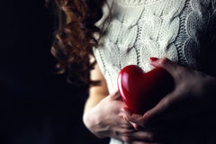 Female hands heart breast love. Object red heart-shaped hands holding a young person royalty free stock photo