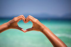 Female hands in heart shape. On sea beach at day time background, Summer season Royalty Free Stock Images