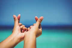 Female hands in heart shape. On sea beach at day time background, Summer season Stock Photo