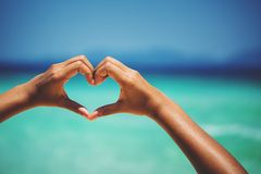 Female hands in heart shape. On sea beach at day time background, Summer season stock image