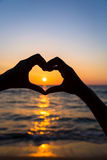 Female hands in heart shape. On sea beach at sunset background, Summer season stock photography