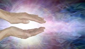 Channelling Vortex spiralling healing energy. Female hands held parallel with a white vortex energy formation and pink blue ethereal energy field  background Stock Image