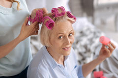 Female hands helping to fix hair rollers. Celebration anticipation. Charming senior women looking at the camera and holding a pink hair roller while her daughter Stock Photos