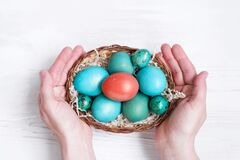 Free Female Hands Hold A Basket Of Bright Easter Eggs Decorated With Spring Flowers On A White Wooden Surface Top View. Stock Images - 185158164