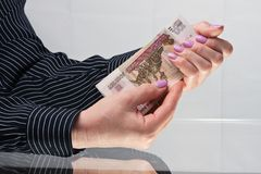 Female hands hold banknotes. Well-groomed female hands with manicure hold banknotes Russian rubles Stock Image