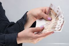 Female hands hold banknotes. Well-groomed female hands with manicure hold banknotes Russian rubles Stock Photo