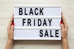 Female hands hold `Black friday sale` word on lightbox over white wooden background, top view. Royalty Free Stock Photo