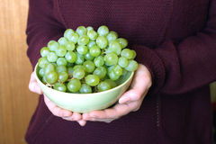 Female hands hold bowl with appetizing green grape Stock Photo