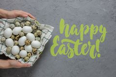 Female hands hold chicken and quail eggs in a plate with a towel on a gray concrete background. Top view. Flat lay. Happy Easter lettering inscription Stock Photos