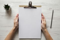 Female hands hold clipboard with sheet of paper, overhead view. Top view, from above royalty free stock photos