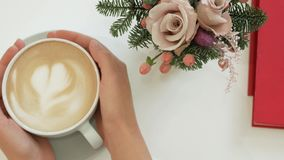 Female hands hold a cup of Cappuccino with a heart on the crema. Coffee with a notebook and a small bouquet on the table. View from above stock images