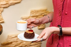 Female hands hold a cup of coffee and cake Royalty Free Stock Photo