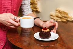 Female hands hold a cup of coffee and cake Stock Photos