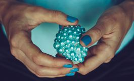 Female hands hold decorated Easter egg. The concept of turquoise color royalty free stock image