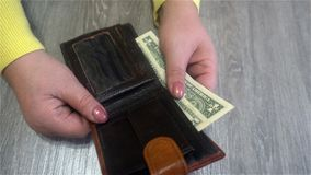 Female hands hold dollar bills from her purse and puts them back into the purse.  Stock Images