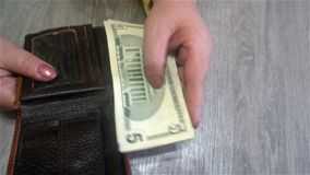 Female hands hold dollar bills from her purse and puts them back into the purse.  Stock Photo