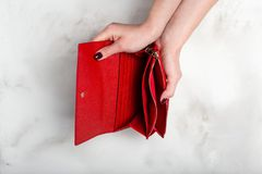 Female hands hold an empty stylish red purse on a white granite stock images