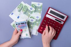 Female hands hold EURO bills and a calculator on a blue background - the concept of accounting. Female hands hold EURO bills and a calculator on a blue Stock Images