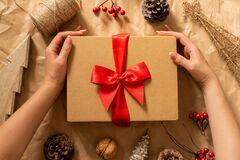 Female hands hold gift box on craft paper background. Winter festive composition with Christmas mood.