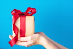 Female hands hold gift box with red bow on a blue background stock photos