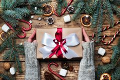 Free Female Hands Hold Gift Box With Bow. Christmas Tree And Decorations, Cane Caramel And Oranges Nuts Wooden Background Royalty Free Stock Photo - 164417305