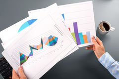 Female hands hold graphic charts. Female employee's hands holding charts. Comparing levels of productivity. It was a difficult year stock photo