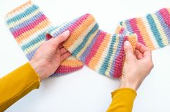 Female hands hold a hand knitted colorful scarf. stock image