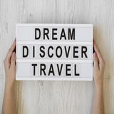 Female hands hold lightbox with text `Dream Discover Travel` over white wooden background, overhead view. From above, flat lay,. Top view stock photography