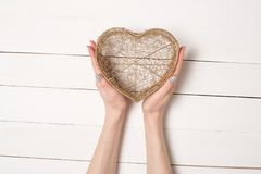 Female hands hold metal wire transparent heart shaped box against the background of a white wooden table.  stock photos