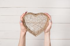 Female hands hold metal wire transparent heart shaped box against the background of a white wooden table.  royalty free stock photography