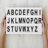Female hands hold modern board with english alphabet over white wooden surface, top view. Close-up.  royalty free stock photography