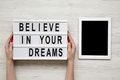 Female hands hold modern board with text `Believe in your dreams`, tablet wit blank screen over white wooden background. From ab. Ove, overhead, flat-lay stock photo