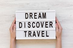 Female hands hold modern board with text `Dream Discover Travel`. Top view. Overhead, from above Royalty Free Stock Photo