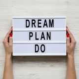Female hands hold modern board with text `Dream plan do` over white wooden background, top view. From above, flat lay, overhead royalty free stock image