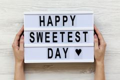 Female hands hold modern board with text `Happy Sweetest Day` word over white wooden background, top view. From above, flat lay royalty free stock image