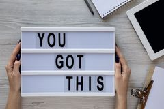 Female hands hold modern board with text `You got this`. Feminine workspace. Business concept. Overhead, top view, from above. royalty free stock images