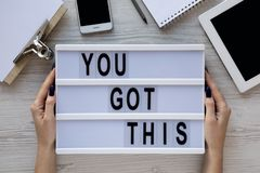 Female hands hold motivation board with text `You got this`. Feminine workspace. Business concept. Overhead, top view, from abov. E stock photo
