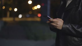 Female hands hold the phone on the background of a night city stock video