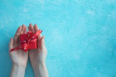 Female hands hold a red gift box with a bow on blue background. Happy Valentine's Day card. stock photography