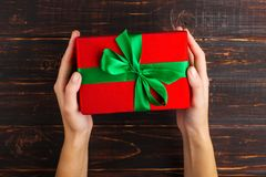 Female hands hold a red gift with a green ribbon. On the background of a wooden table, top view. Female hands hold red gift with a green ribbon. On the stock photography