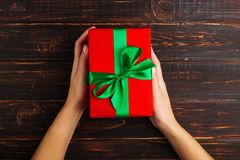 Female hands hold a red gift with a green ribbon. On the background of a wooden table, top view. Female hands hold a red gift with a green ribbon. On the royalty free stock image