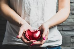 Female hands hold a red metal heart. Concept of love. Valentine`s Day, Valentine`s day. Gifts for occasions, love, showing love and cordiality stock photography